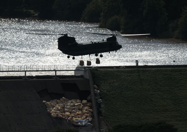 An RAF Chinook helicopter drops aggregate to help shore up a reservoir at risk of collapse, threatening to engulf the town of Whaley Bridge in the Peak District, England, 2 August 2019