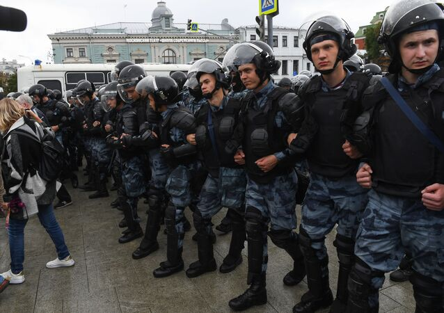 Law enforcement officers block the street during the rally in support of the registration of independent candidates for the September's elections to the Moscow City Duma, in downtown Moscow, Russia.