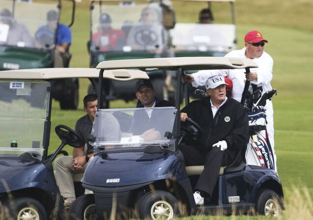 US President Donald Trump rides a golf buggy, at Turnberry golf club, in Turnberry,  Scotland