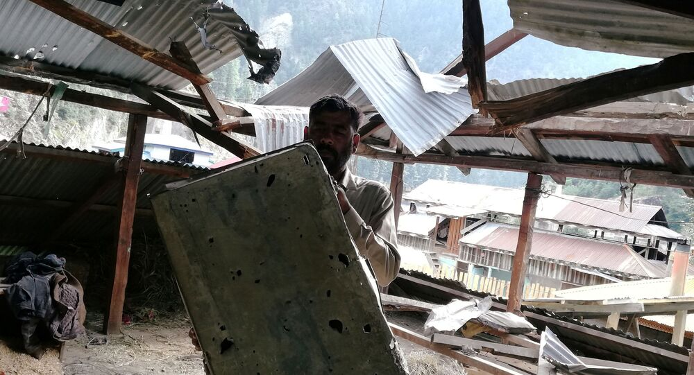A resident shows a riddled metal suitcase as he stands under a damaged roof of a house in Salkhala village, in Neelum Valley