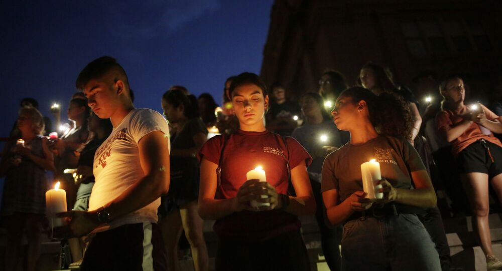 Samuel Lerma, Arzetta Hodges and Desiree Qunitana join mourners taking in a vigil at El Paso High School after a mass shooting at a Walmart store in El Paso, Texas, U.S. August 3, 2019