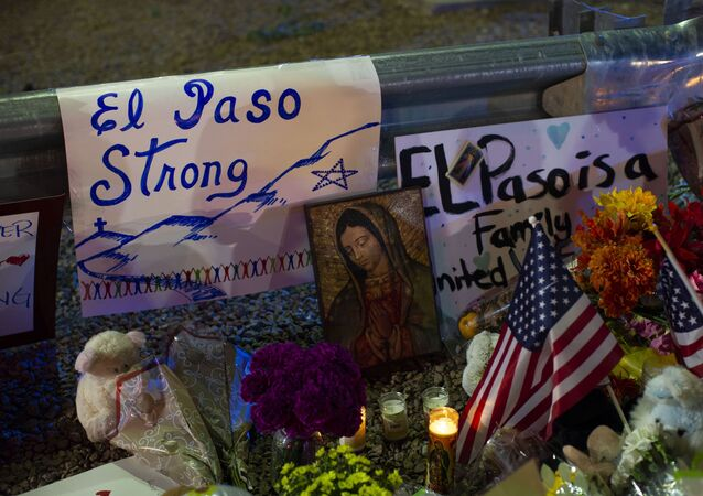 A Virgin Mary painting, flags and flowers adorn a makeshift memorial for the victims of Saturday's mass shooting at a shopping complex in El Paso, Texas, Sunday, Aug. 4, 2019