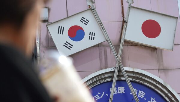 A woman walks past an advertisement featuring Japanese and South Korean flags at a shop in Shin Okubo area in Tokyo Friday, Aug. 2, 2019 - Sputnik International