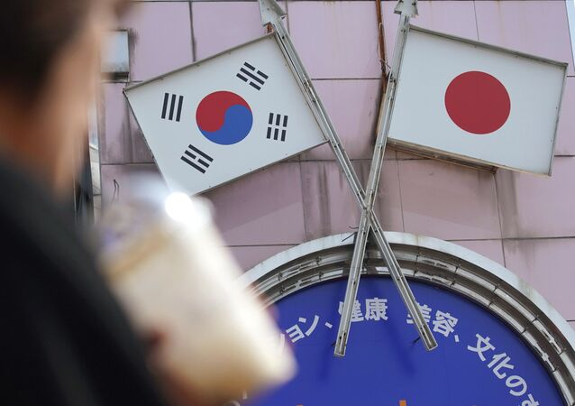 A woman walks past an advertisement featuring Japanese and South Korean flags at a shop in Shin Okubo area in Tokyo Friday, Aug. 2, 2019