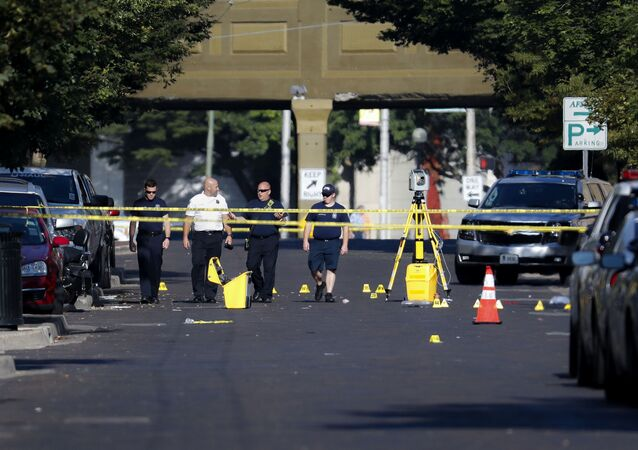 Authorities walk among evidence markers at the scene of a mass shooting, Sunday, Aug. 4, 2019, in Dayton, Ohio. Severral people in Ohio have been killed in the second mass shooting in the U.S. in less than 24 hours, and the suspected shooter is also deceased, police said