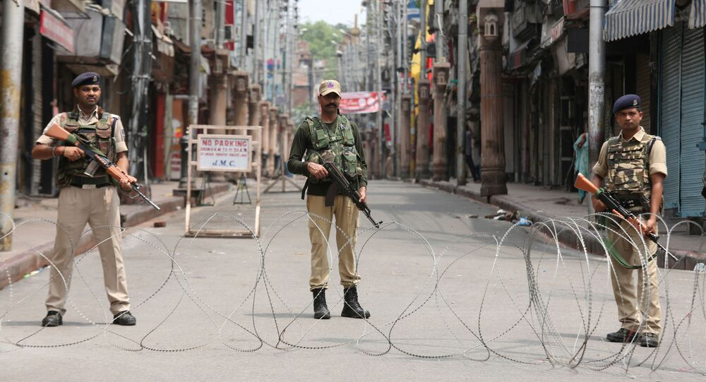 Indian security personnel stand guard along a deserted street during restrictions in Jammu, August 5, 2019