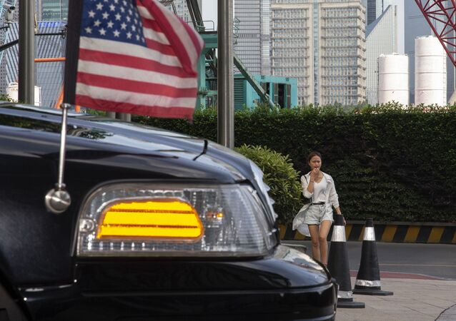 A woman walks towards a U.S. embassy car outside a hotel in Shanghai on Tuesday, July 30, 2019