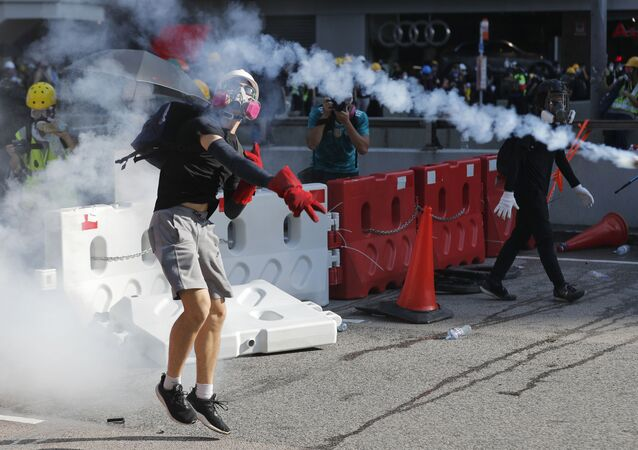 A protester throws back a tear gas canister in Hong Kong on Monday, Aug. 5, 2019. Droves of protesters filled public parks and squares in several Hong Kong districts on Monday in a general strike staged on a weekday to draw more attention to their demands that the semi-autonomous Chinese city's leader resign