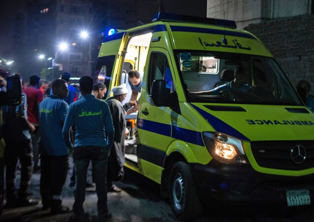 A rescuer helps a man to board an ambulance during the night of August 5, 2019, at the scene of an accident that took place just before midnight on August 4, outside the National Cancer Institute in the Egyptian capital Cairo