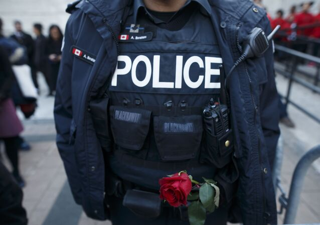 A Toronto Police Officer holds a rose in his belt during a vigil for the victims  (File)