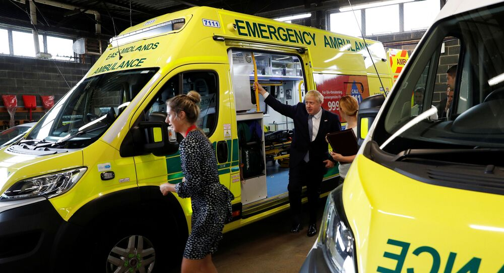 Britain's Prime Minister Boris Johnson holds on to an ambulance during a visit to Pilgrim Hospital in Boston, UK, 5 August 2019