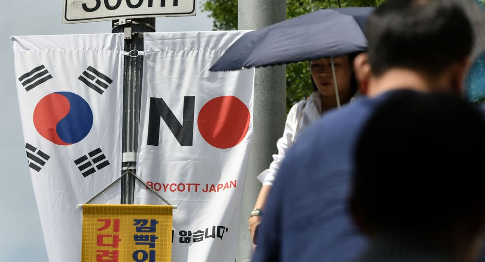 Pedestrians walk past a South Korean flag (L) and a banner (R) that reads Boycott Japan hanging along a street in Seoul's Jung-gu district on August 6, 2019.