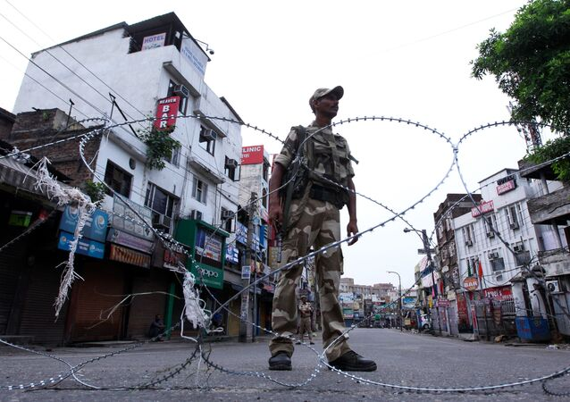 A security personnel stands guard on a street in Jammu on August 6, 2019