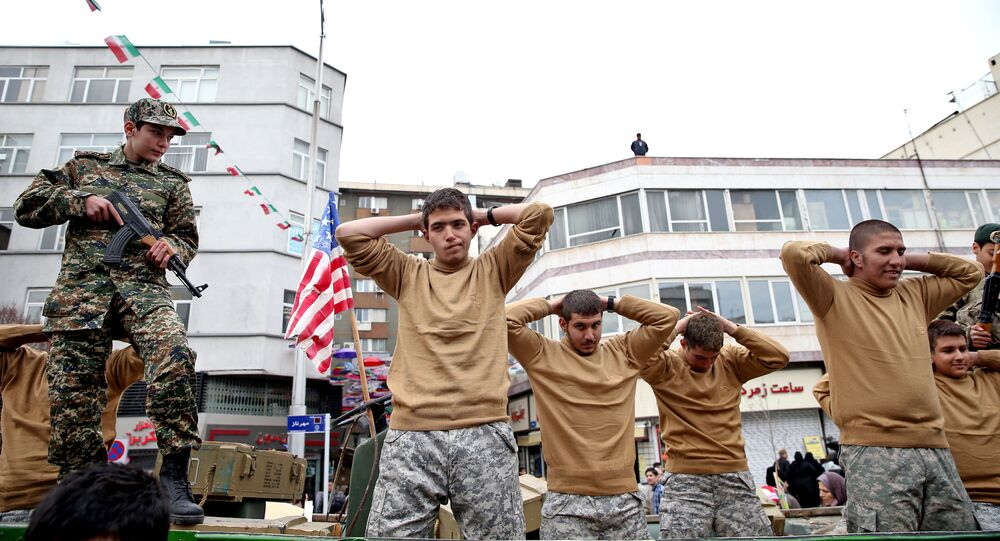 FILE - In this Thursday, Feb. 11, 2016 file photo, members of Iranian Basij paramilitary force re-enact the January capture of U.S sailors by the Revolutionary Guard in the Persian Gulf, in a rally commemorating the 37th anniversary of Islamic Revolution in Tehran, Iran The nationwide rallies commemorate Feb. 11, 1979, when followers of Ayatollah Khomeini ousted U.S.-backed Shah Mohammad Reza Pahlav