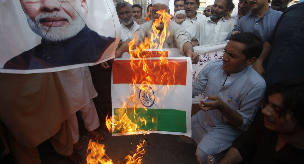 Pakistanis burn a sign featuring an Indian flag as well as a poster of Indian Prime Minster Narendra Modi during a protest to express support and solidarity with India's Kashmiri people in their peaceful struggle for their right to self-determination, in Peshawar, Pakistan, Monday, 5 August 2019