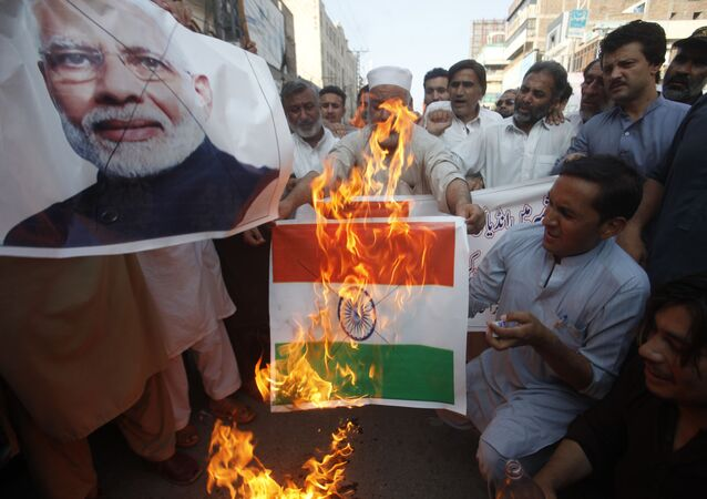 Pakistanis burn a representation of an Indian flag and a poster of Indian Prime Minster Narendra Modi during a protest to express support and solidarity with Indian Kashmiri people in their peaceful struggle for their right to self-determination, in Peshawar, Pakistan, Monday, 5 August 2019.