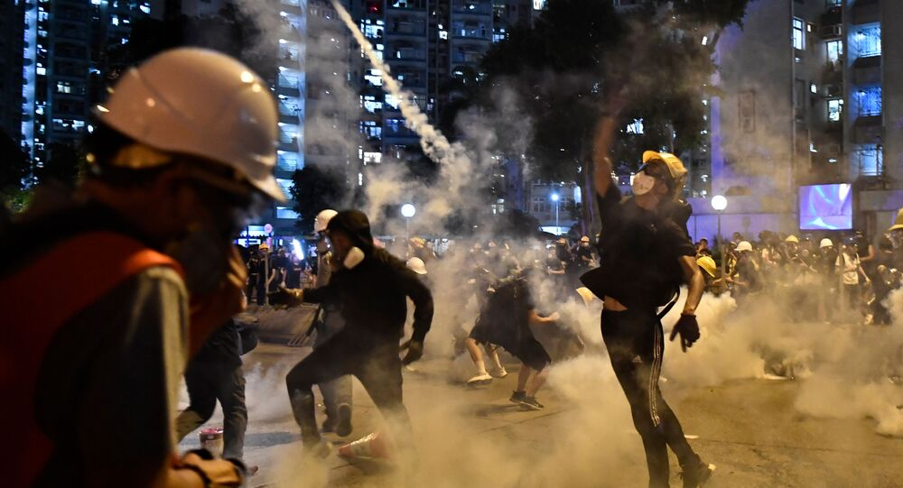 Protesters throw back tear gas fired by the police in Wong Tai Sin during a general strike in Hong Kong on August 5, 2019, as simultaneous rallies were held across seven districts.