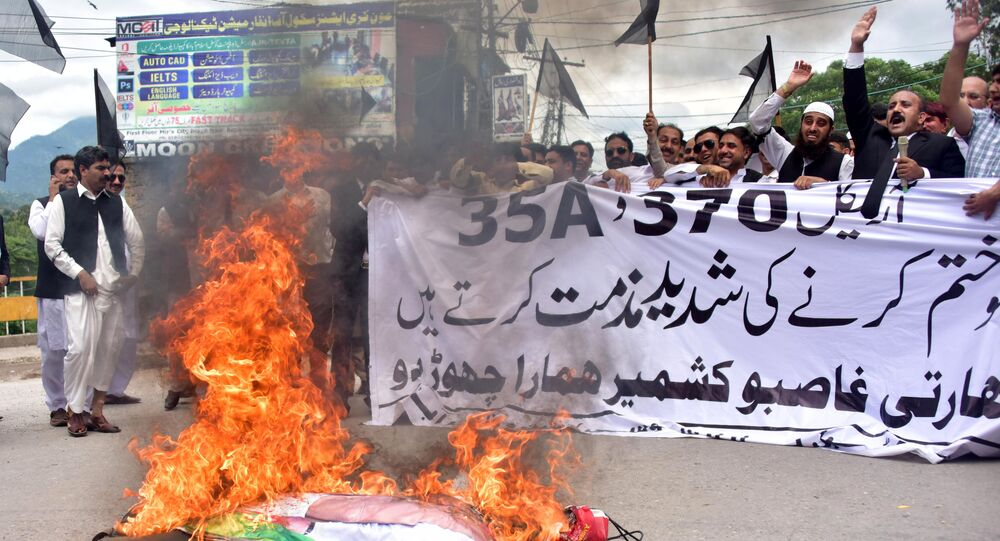 Pakistani Kashmiri lawyers shout slogans beside a burning effigy of Indian Prime Minister Narendra Modi during a protest in Muzaffarabad, the capital of Pakistan-controlled Kashmir, on August 7, 2019.
