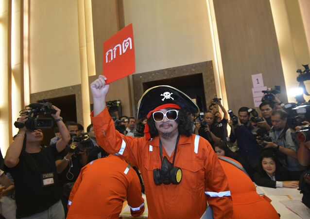 A political activist Sombat Boonngamanong dressed as a pirate holds a card in protest reading Election Commission Bangkok, Thailand, Friday, Sept. 28, 2018.