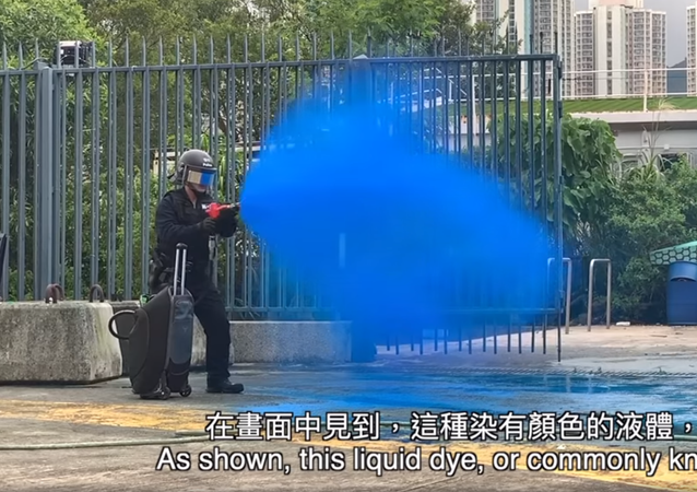 Hong Kong police official demonstrating the proper way to spray the new liquid dye used to tag and identify protesters