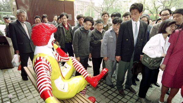 Passers-by keep their distance from Ronald McDonald as he sits outside the first McDonalds restaurant to be opened in Beijing on April 20, 1992. - Sputnik International