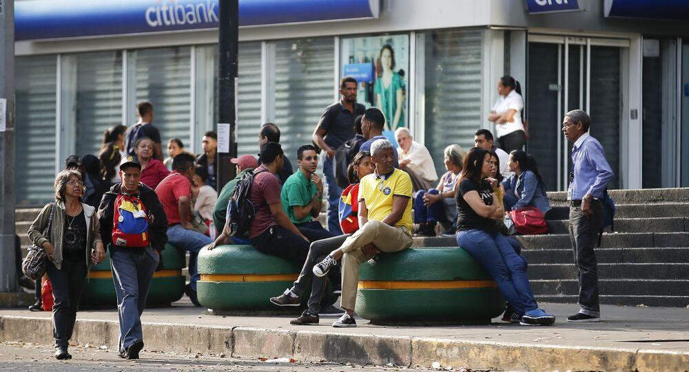 People wait for public transportation in Caracas, Venezuela, Friday, March 8, 2019