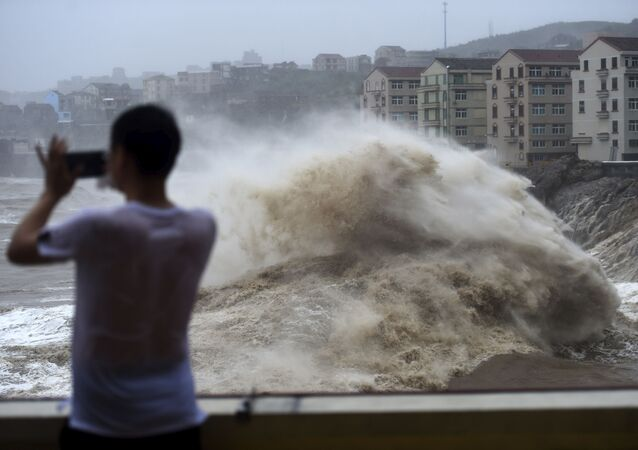 In this Aug. 9, 2019, photo released by Xinhua News Agency, a man uses his mobile phone to record waves crashing on the shore as typhoon Lekima approaches the Shitang Township of Wenling City in eastern China's Zhejiang Province.