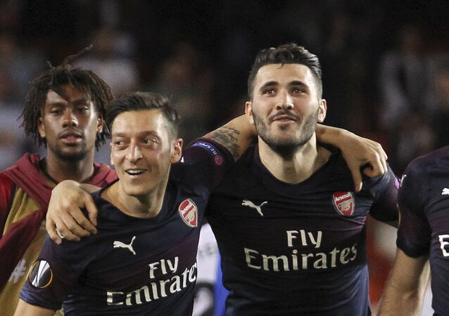 FILE - In this Thursday, May 9, 2019 file photo, Arsenal defender Sead Kolasinac, right celebrates with Arsenal midfielder Mesut Ozil, left, at the end of the Europa League semifinal soccer match, second leg, between Valencia and Arsenal at the Camp de Mestalla stadium in Valencia, Spain.