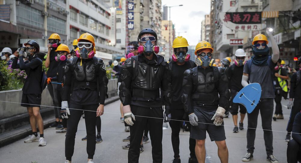 Protesters with protection gears face with riot policemen on a street during the anti-extradition bill protest in Hong Kong, Sunday, Aug. 11, 2019. Police fired tear gas late Sunday afternoon to try to disperse a demonstration in Hong Kong as protesters took over streets in two parts of the Asian financial capital, blocking traffic and setting up another night of likely showdowns with riot police.