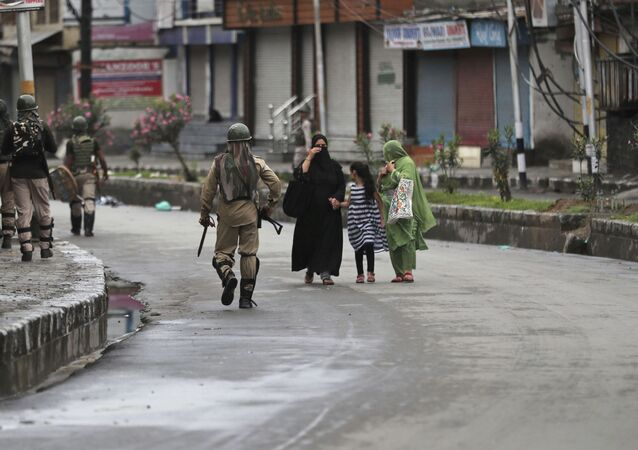 Kashmiris walks past Indian paramilitary soldiers patrolling a street in Srinagar, Indian controlled Kashmir, Saturday, Aug. 10, 2019