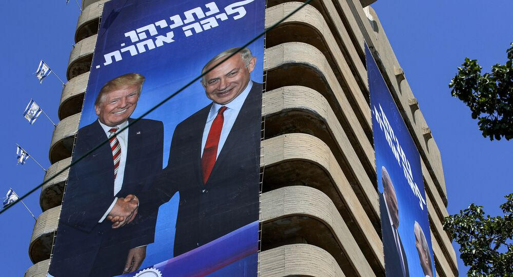 This picture taken on July 28, 2019 shows two giant Israeli Likud Party election banners hanging from a building showing Israeli Prime Minister Benjamin Netanyahu shaking hands with US President Donald Trump (L) and Russian President Vladimir Putin, with a caption above reading in Hebrew Netanyahu, in another league, in the coastal Mediterranean city of Tel Aviv.