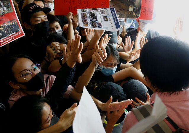 Anti-government protesters try to prevent a passenger from breaching a barricade in front of departure gates, during a demonstration at Hong Kong Airport, China August 13, 2019.