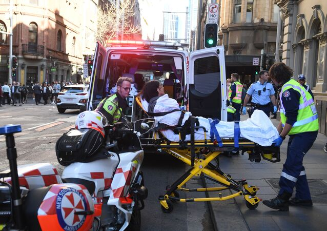 A women is taken by ambulance from Hotel CBD at the corner of King and York Street in Sydney, Australia Tuesday, Aug. 13, 2019. Police and witnesses say a young man yelling about religion and armed with a knife has attempted to stab several people in downtown Sydney before being arrested, with one woman taken to a hospital.