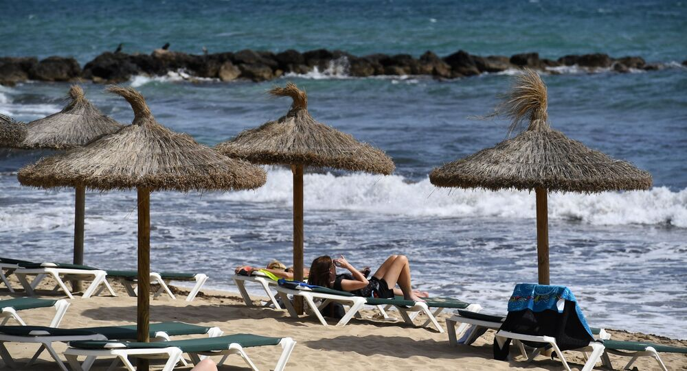 People sunbath on May 9, 2019 on a beach of the Spanish Balearic island of Majorca near Palma
