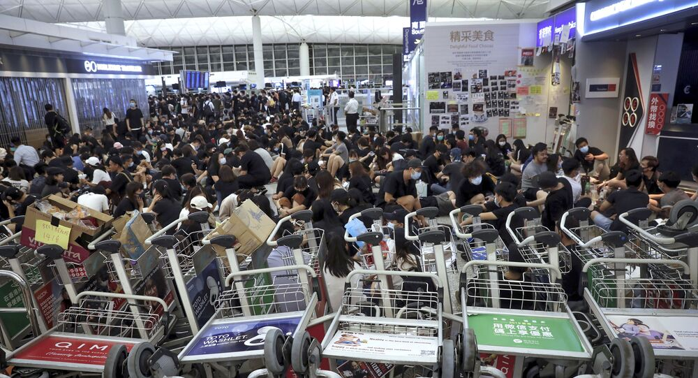 Protesters use luggage trolleys to block the walkway to the departure gates during a demonstration at the Airport in Hong Kong