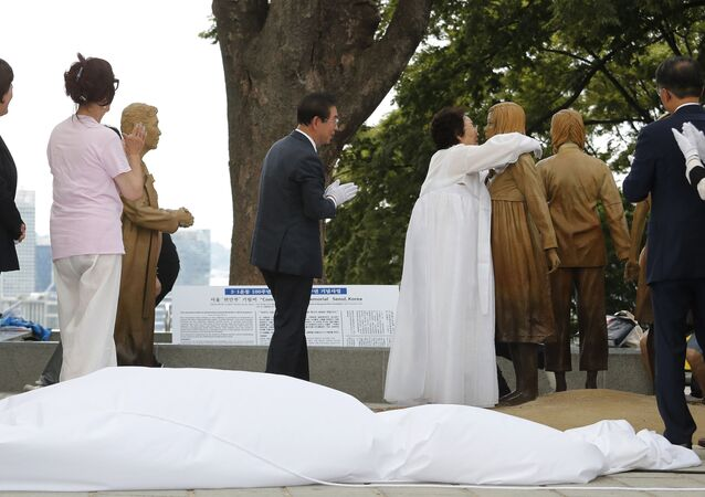 Lee Yong-soo, second from right, who was forced to serve for the Japanese troops as a sex slave during World War II, hugs a statue of a girl symbolising the issue of wartime comfort women during it unveiling ceremony in Seoul, South Korea, Wednesday, Aug. 14, 2019.