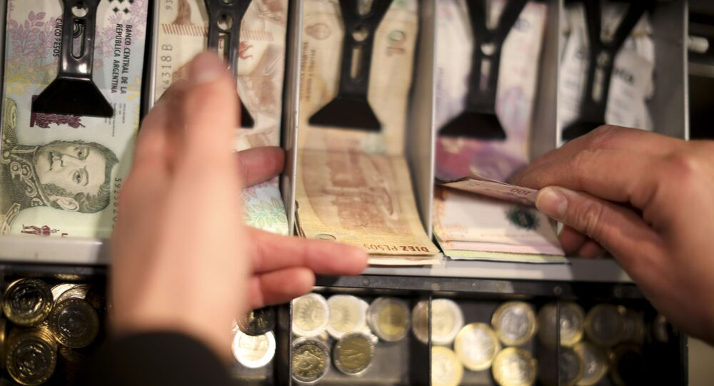 A man holds a 100 peso bill in the cashier of a restaurant in Buenos Aires, Argentina, Wednesday, Aug. 14, 2019. President Mauricio Macri announced economic relief for poor and working-class Argentines that include an increased minimum wage, reduced payroll taxes, a bonus for informal workers and a freeze in gasoline prices. The conservative leader said Wednesday he's acting in recognition of the anger Argentines expressed in Sunday's primary election, when Macri trailed his populist rival by 15 percentage points.