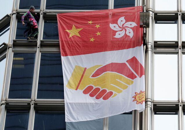 French urban climber Alain Robert climbs the Cheung Kong Centre building in Hong Kong, China