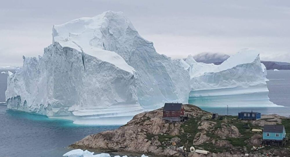 A picture taken on July 13, 2018 shows an iceberg behind houses and buildings after it grounded outside the village of Innarsuit, an island settlement in the Avannaata municipality in northwestern Greenland.