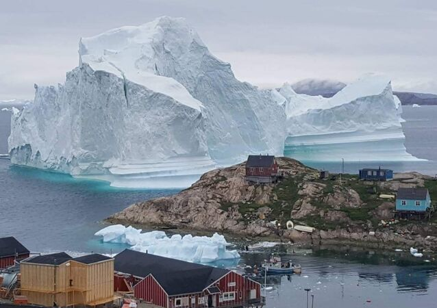 A picture taken on 13 July 2018 shows an iceberg behind houses and buildings after it grounded outside the village of Innarsuit, an island settlement in the Avannaata municipality in northwestern Greenland.