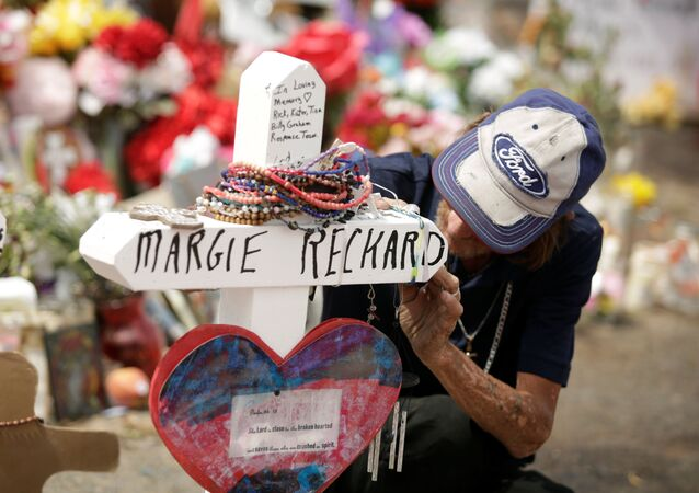 Antonio Basco, whose wife Margie Reckard was murdered during a shooting at a Walmart store, touches a white wooden cross bearing the name of his late wife, at a memorial for the victims of the shooting in El Paso, Texas, U.S.