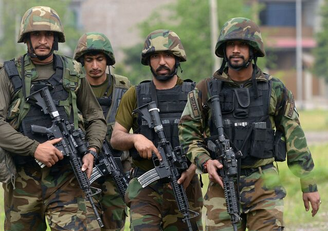 Pakistani soldiers walk from a site after an operation against suspected militants in Peshawar on April 16, 2019