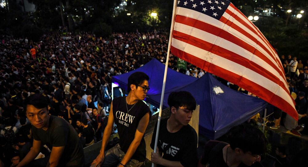 Anti-extradition bill protesters hold an American flag at a gathering at Chater House Garden in Hong Kong on August 16, 2019. - Hong Kong's pro-democracy movement faces a major test this weekend as it tries to muster another huge crowd following criticism over a recent violent airport protest and as concerns mount over Beijing's next move.