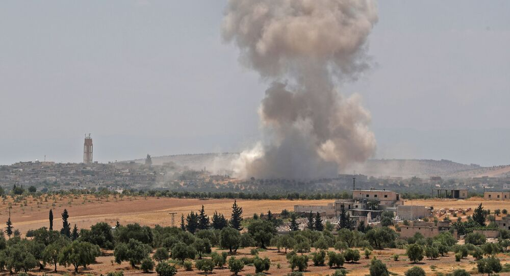 Smoke billows above buildings near the town of Hish in Syria's Idlib province