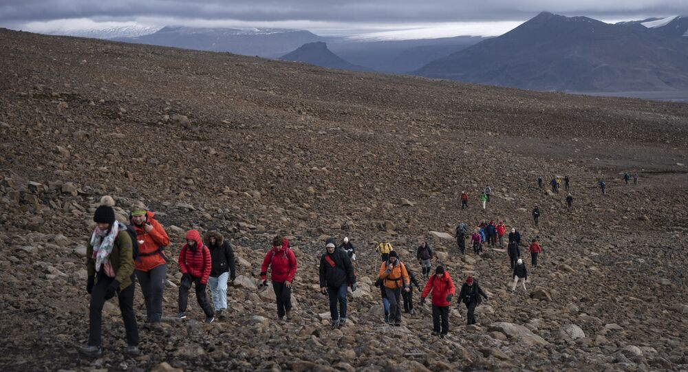 People climb to the top of what once was the Okjokull glacier, in Iceland, Sunday, Aug. 18, 2019. With poetry, moments of silence and political speeches about the need to fight climate change, Icelandic officials, activists and others bade goodbye to the first Icelandic glacier to disappear. (AP Photo/Felipe Dana)