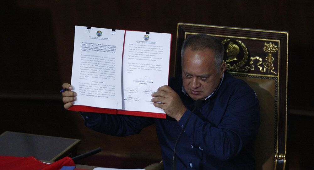 Venezuela's President of the National Constituent Assembly Diosdado Cabello shows a document protesting U.S. sanctions during a session by the legislative body that is stacked with government allies that rivals the opposition-controlled National Assembly in Caracas, Venezuela, Monday, Aug. 12, 2019. The United States froze all Venezuelan government assets in the U.S., putting the country on a short list of U.S. adversaries.