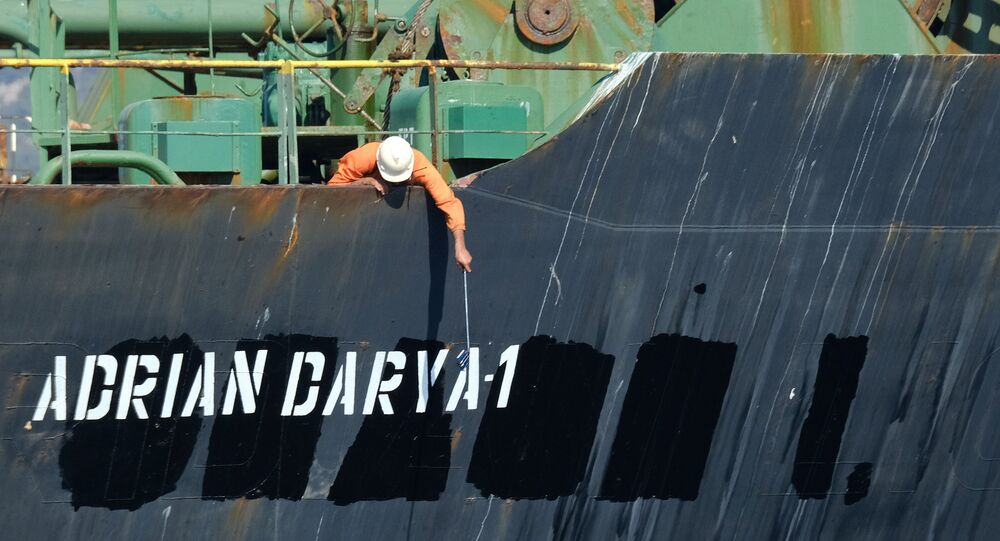 A crew member checks the new name of Iranian oil tanker Adrian Darya, formerly known as Grace 1, off the coast of Gibraltar on 18 August 2019. - Gibraltar rejected a US demand to seize the Iranian oil tanker at the centre of a diplomatic dispute as it prepared to leave the British overseas territory after weeks of detention.