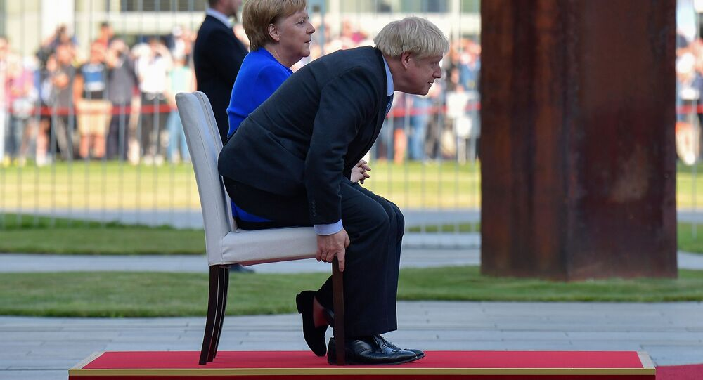 German Chancellor Angela Merkel and British Prime Minister Boris Johnson sit for the national anthems during a ceremony with military honours at the Chancellery on his first foreign visit since taking office on August 21, 2019 in Berlin