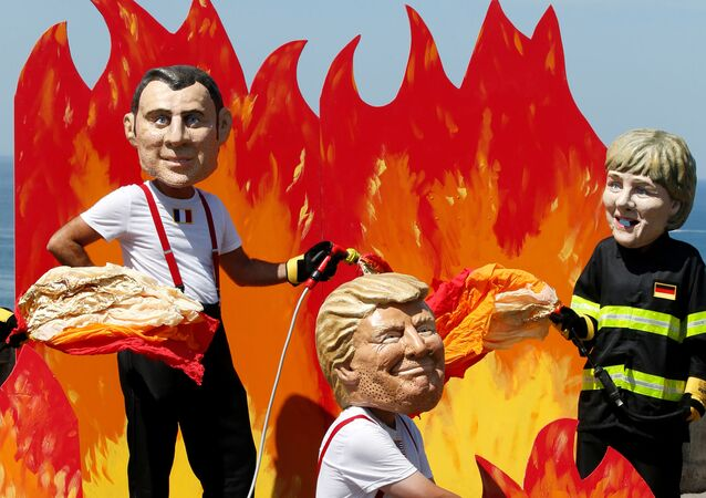 Oxfam activists wearing giant papier mache heads depicting G7 leaders U.S. President Donald Trump , French President Emmanuel Macron and German Chancellor Angela Merkel pose dressed as firemen to draw attention to fighting inequality, on the eve of the G7 summit in Biarritz, France, August 23, 2019.
