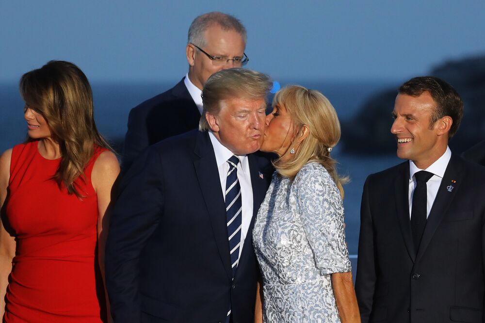 French President's wife Brigitte Macron kisses US President Donald Trump, flanked by US First Lady Melania Trump and France's President Emmanuel Macron, prior to a family picture with G7 leaders and guests, on the second day of the annual G7 summit in Biarritz, south-west France on August 25, 2019.